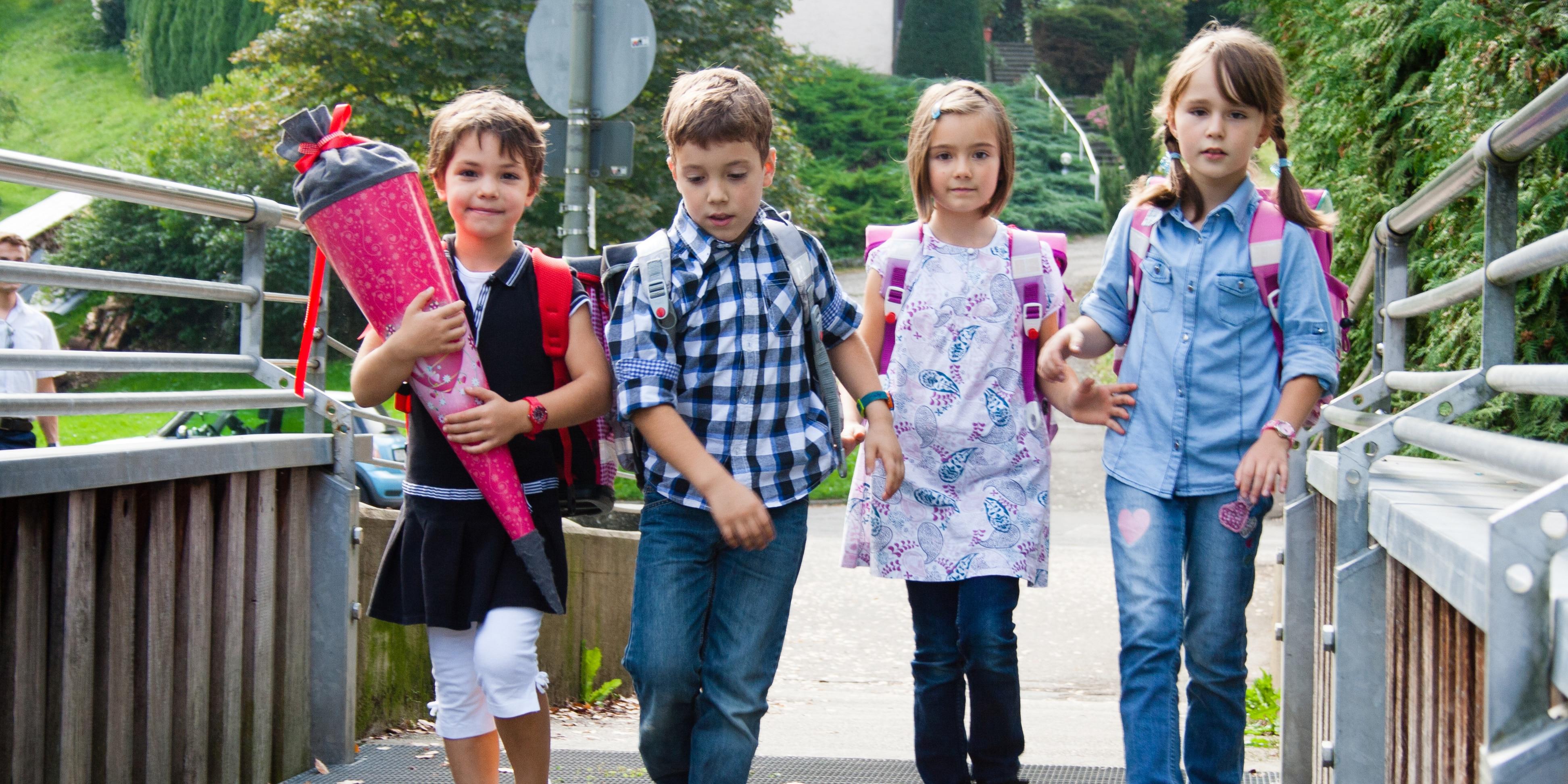vier Schulkinder gehen in einer Reihe über eine Brücke