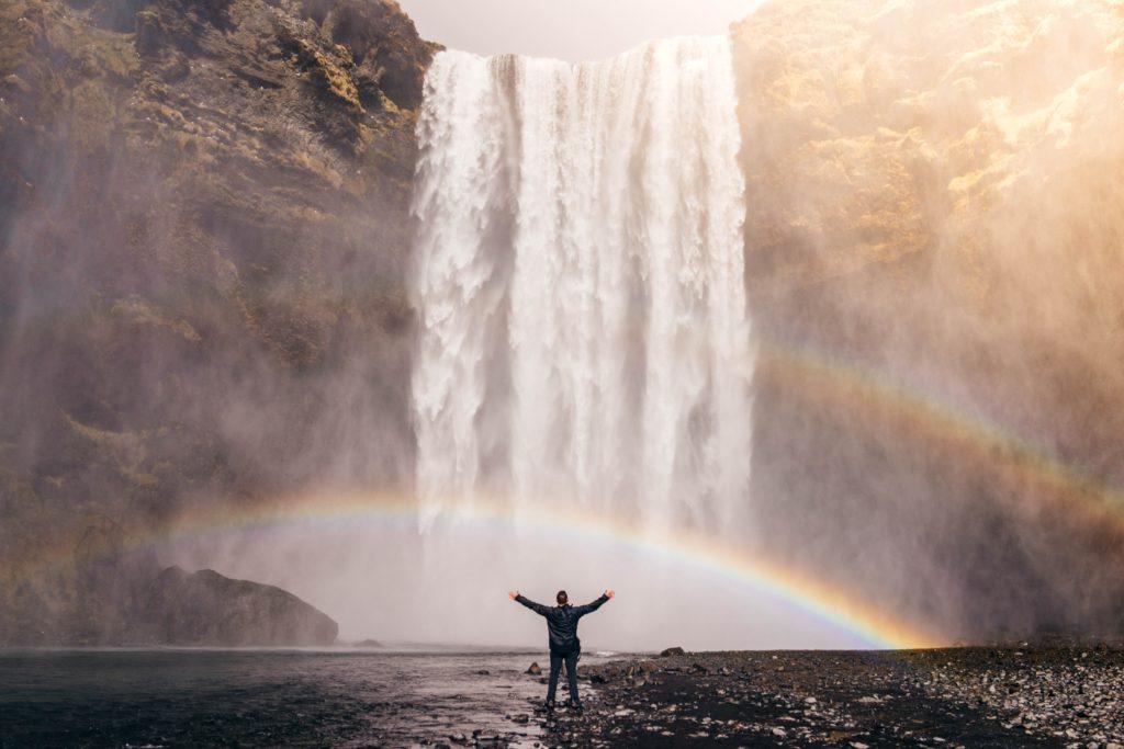 Ein Mann steht vor einem Wasserfeld. Es ist ein Regenbogen zu sehen.