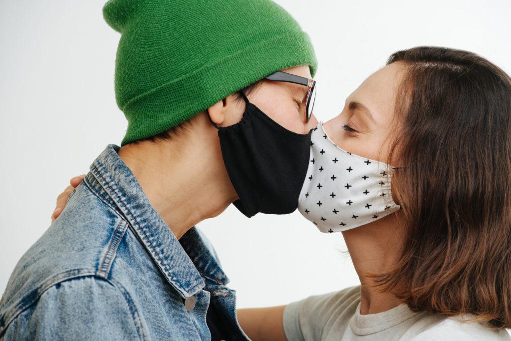 Zwei Menschen mit Maske küssen sich