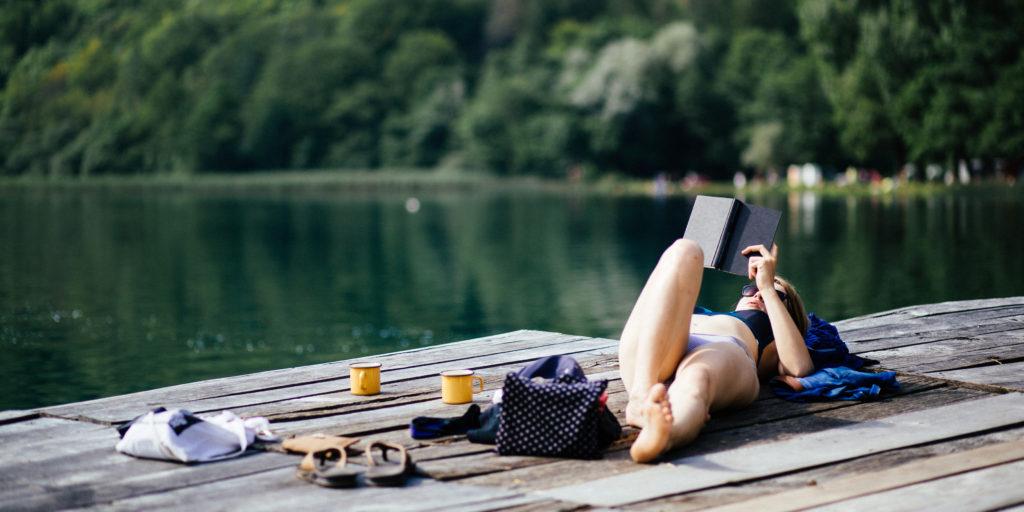 Frau im Bikini liegt auf einem Steg und liest ein Buch