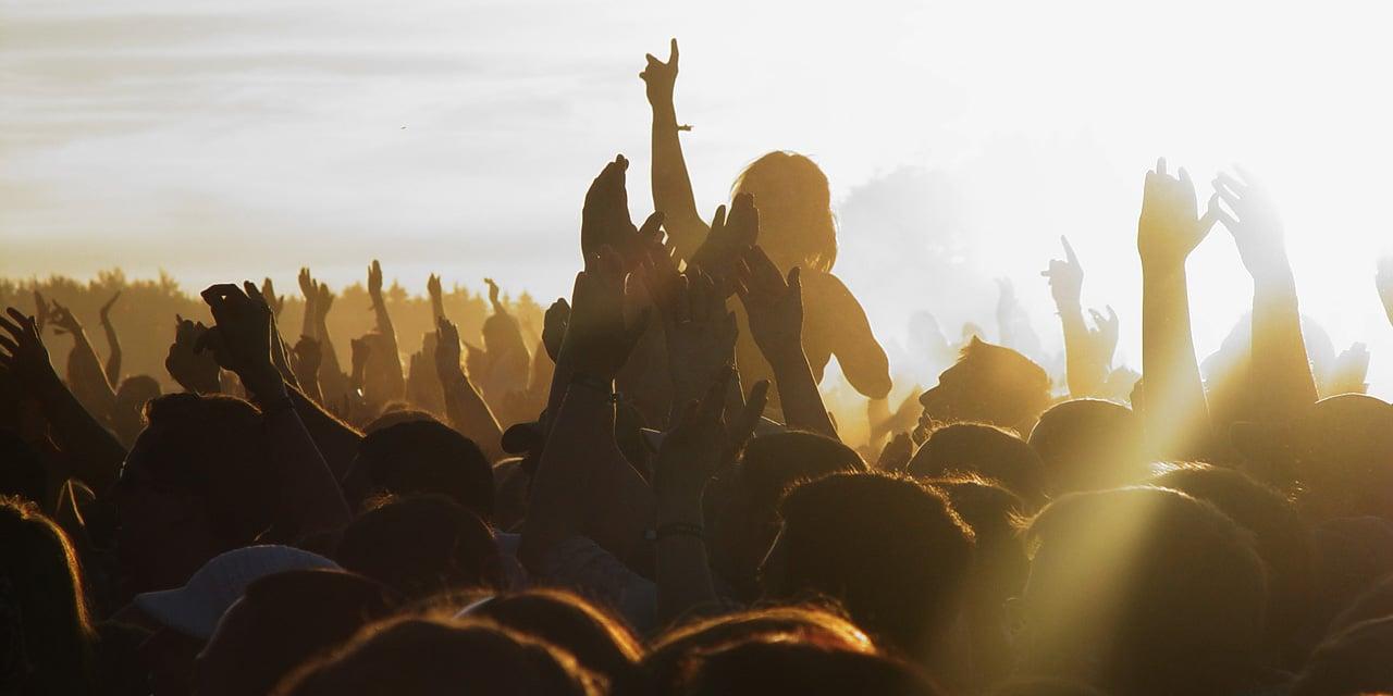 Festivalbesucher mit erhobenen Händen im Sonnenuntergang