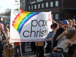 """Eine Gruppe von Demonstranten hält eine Fahne mit der Aufschrift """"Pax Christi"""" und einem Regenbogen in die Luft."""