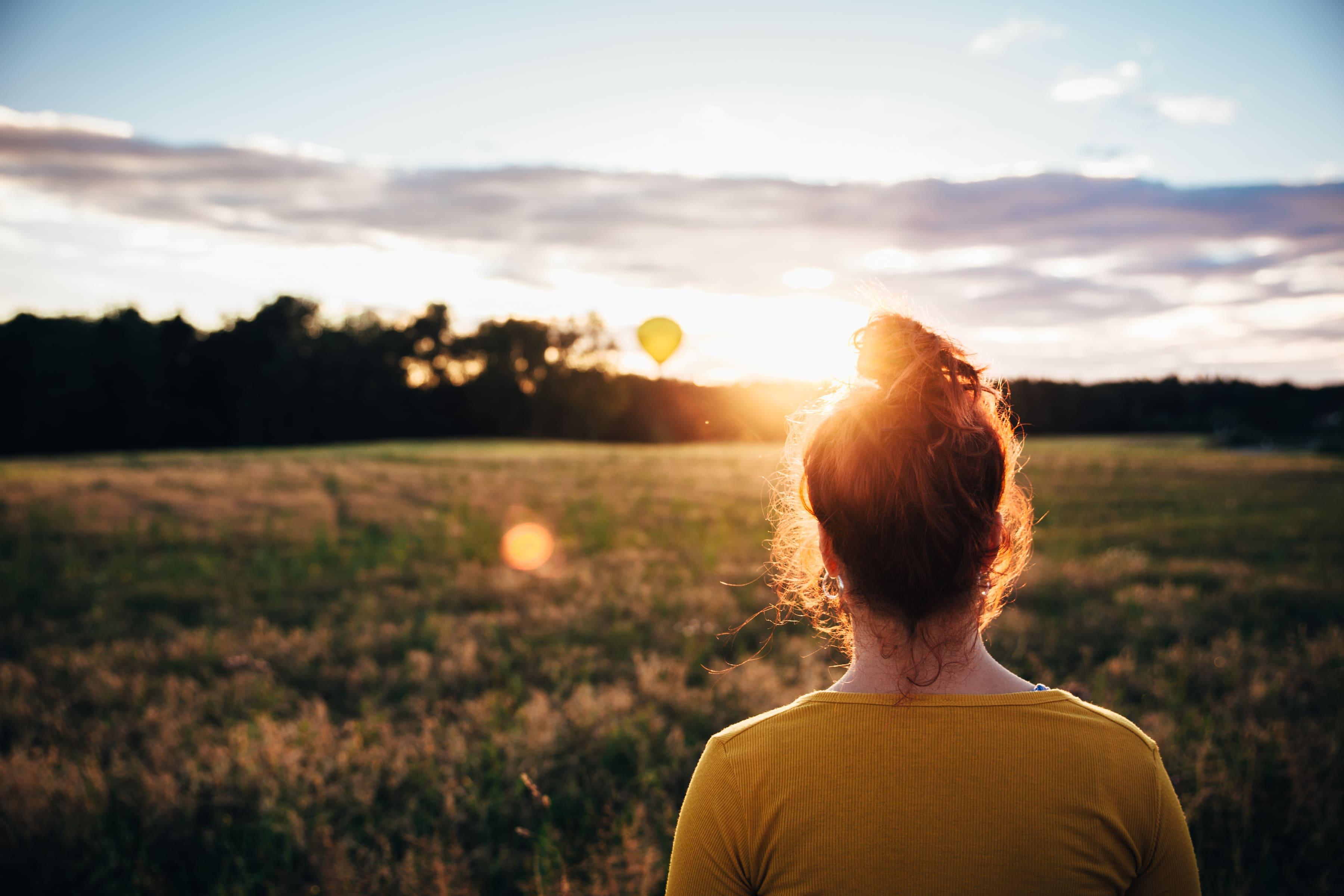 Rücken einer jungen Frau im Abendlicht