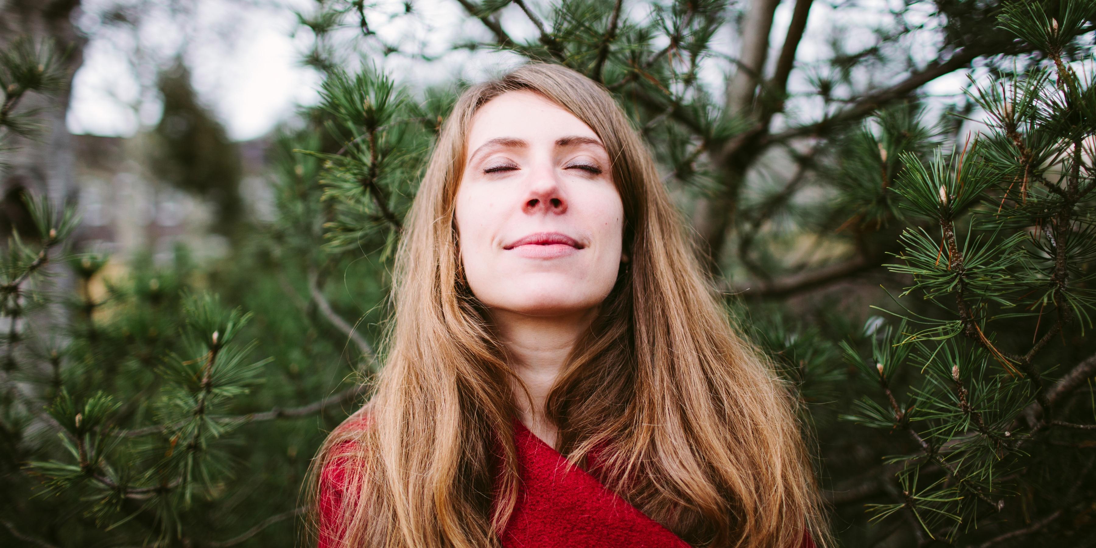 Frau mit geschlossenen Augen atmet tief durch