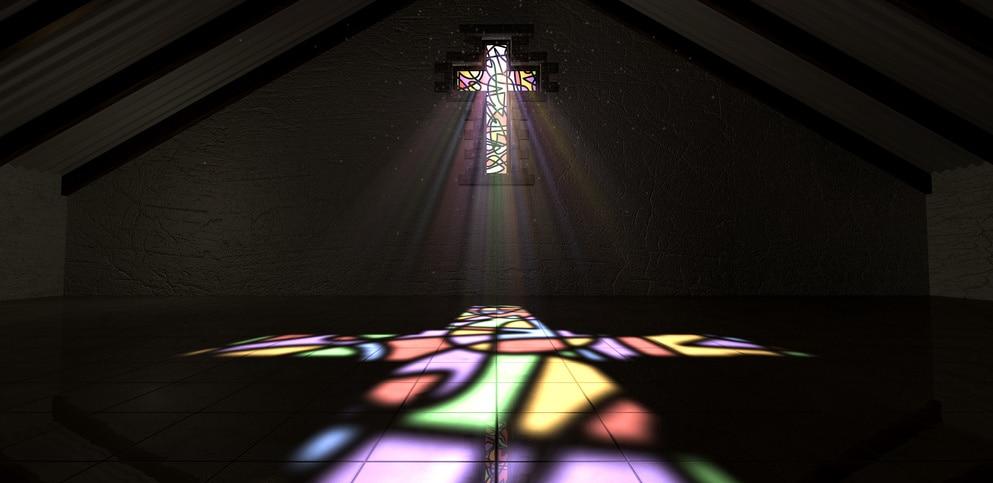 Sonnenstrahlen scheinen durch ein großes, buntes Fenster in Kreuzform