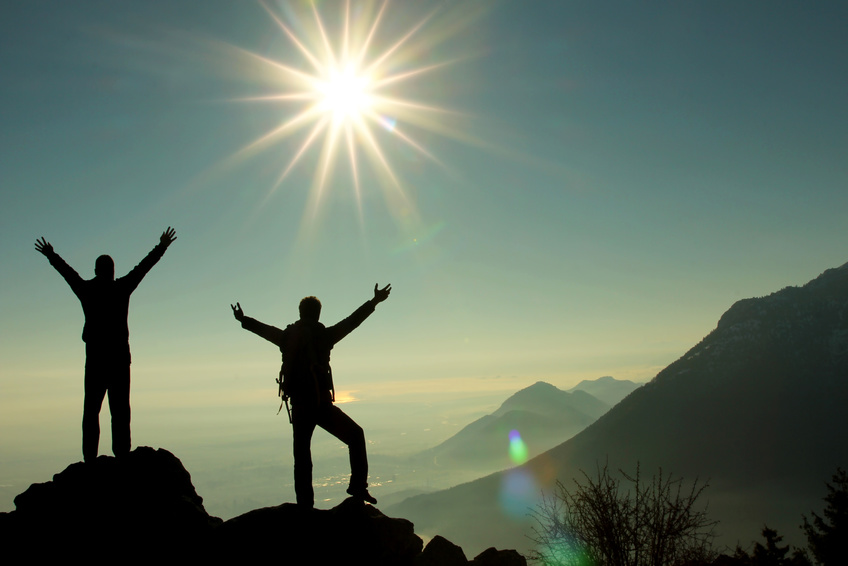 zwei Bergsteiger auf einem Gipfel strecken die Arme zur Sonne