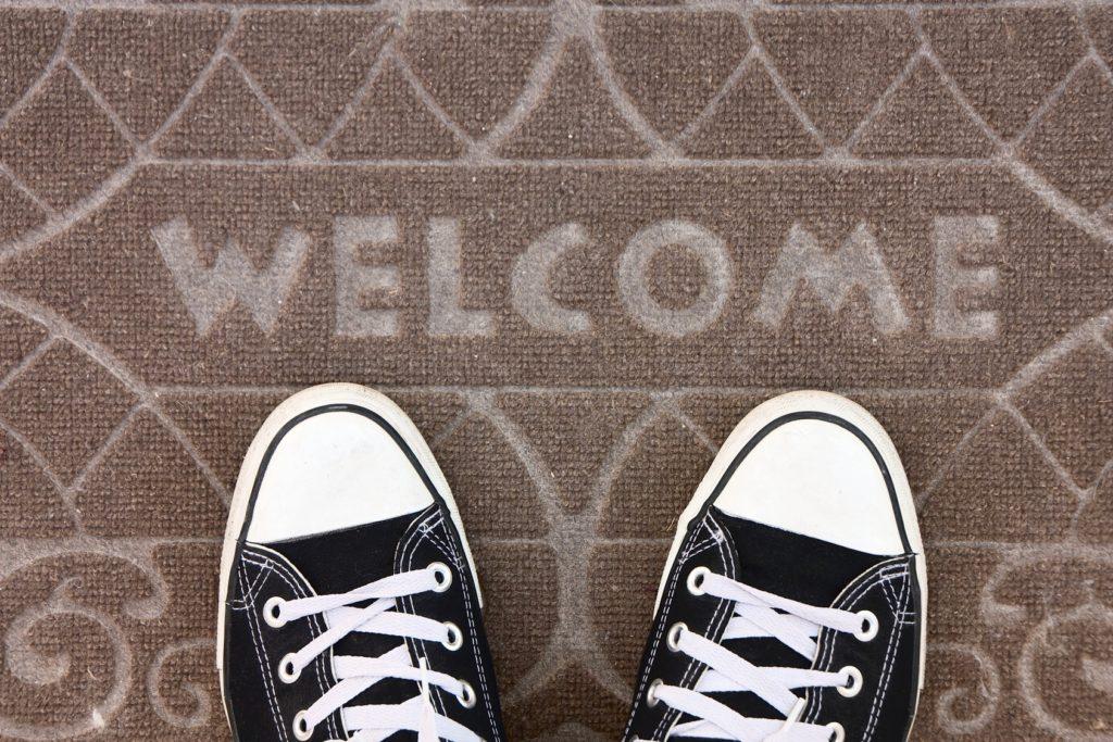 """Zwei Füße auf einer Fußmatte auf der """"Welcome"""" steht"""