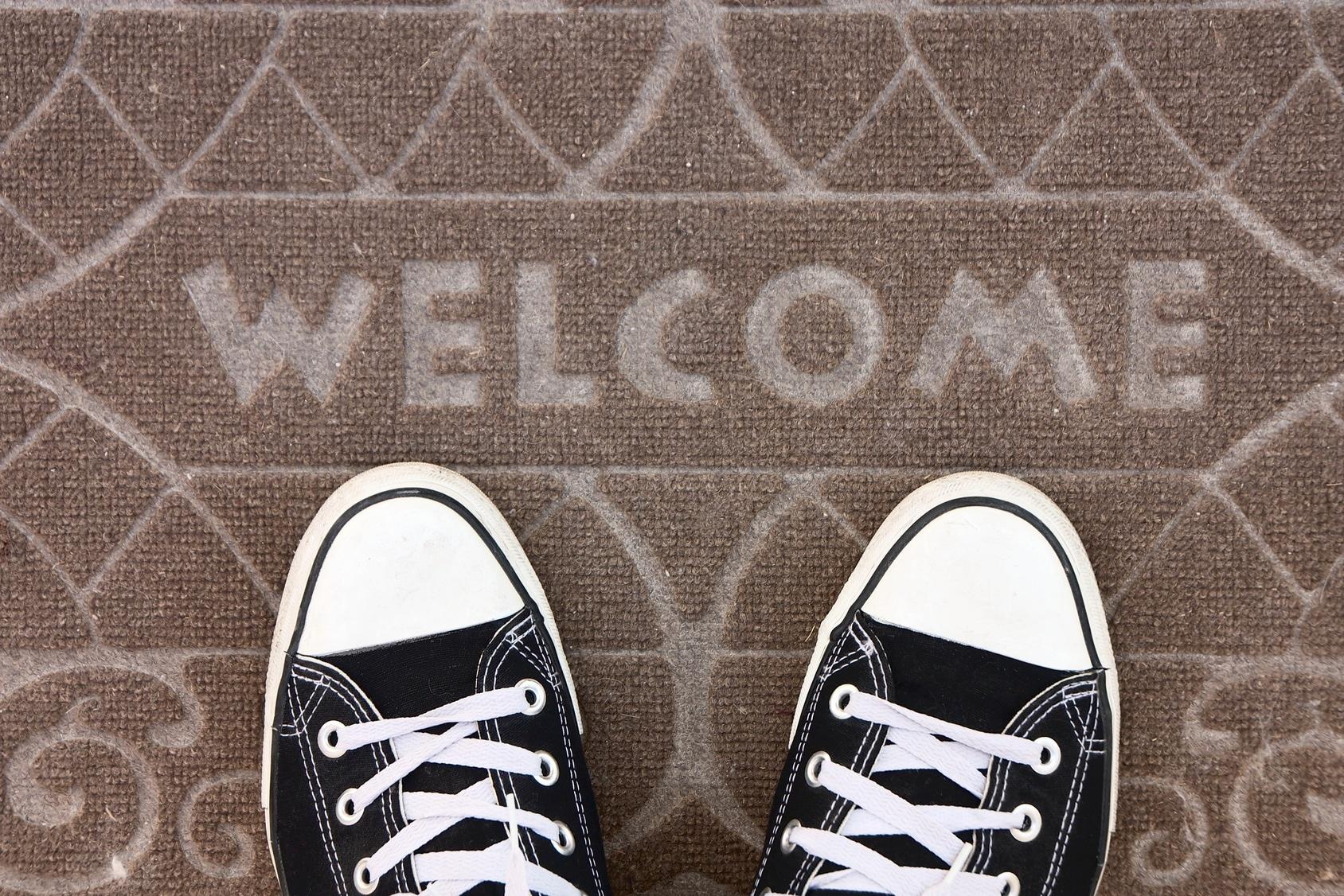 Zwei Füße auf einer Fußmatte auf der 'Welcome' steht