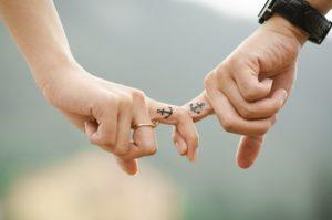 zwei Menschenhalten sich an den Zeigefingern, auf denen jeweils ein Anker tättowiert ist