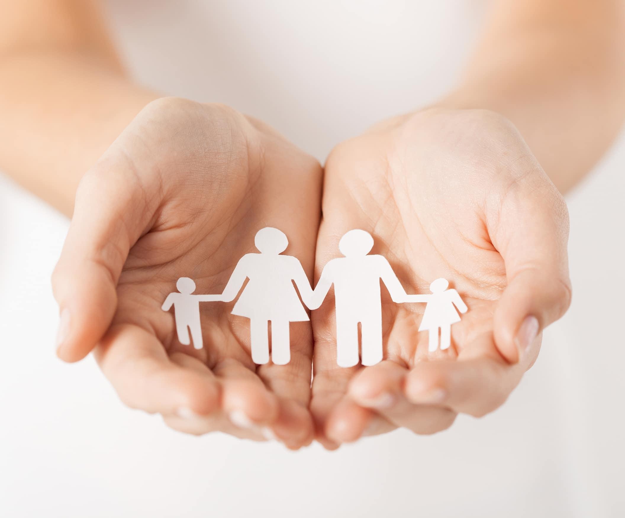 Familie aus Papier liegt in geöffneten Händen