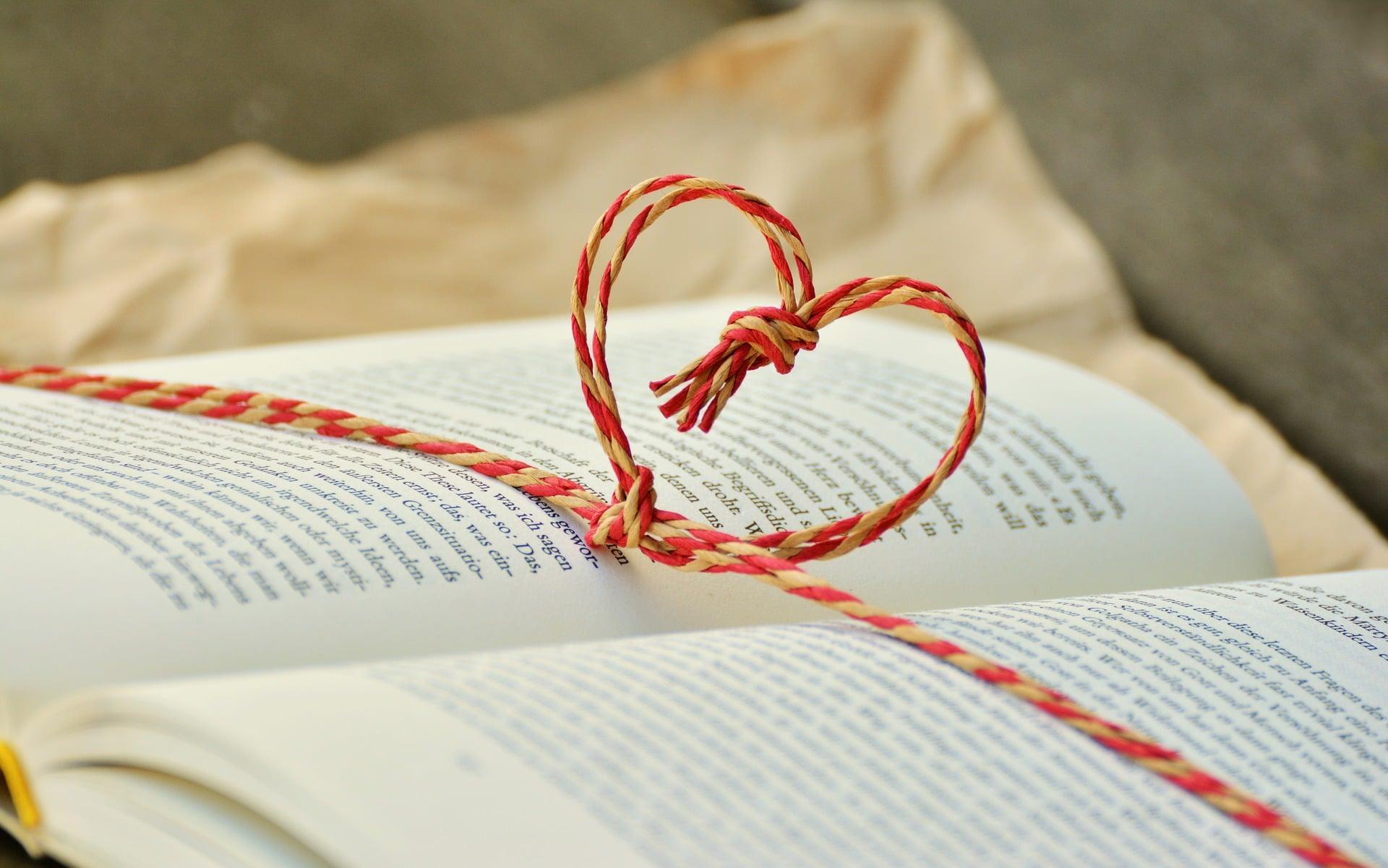 Ein aufgeschlagenes Buch mit einem Herz aus Schnüren