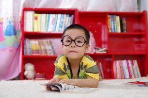 Kind mit Brille blickt aus einem Buch auf