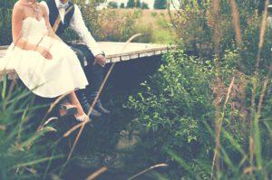 Hochzeitspaar sitzt auf einer Brücke