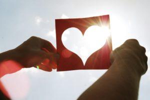 Sonnenstrahlen fallen durch eine Herzschablone, die von zwei Händen gehalten wird
