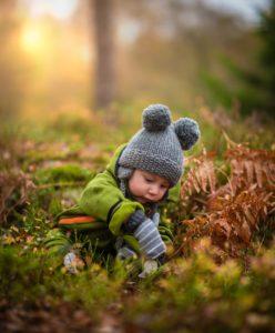 Kind sitzt im Wald