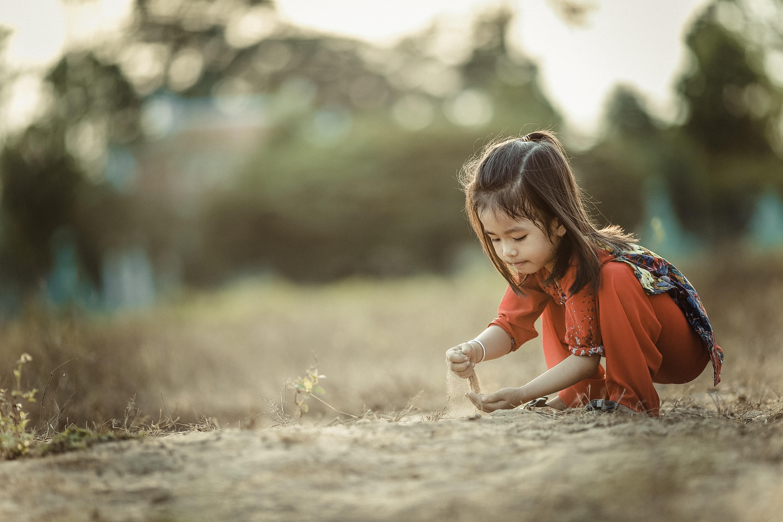 Mädchen spielt im Sand