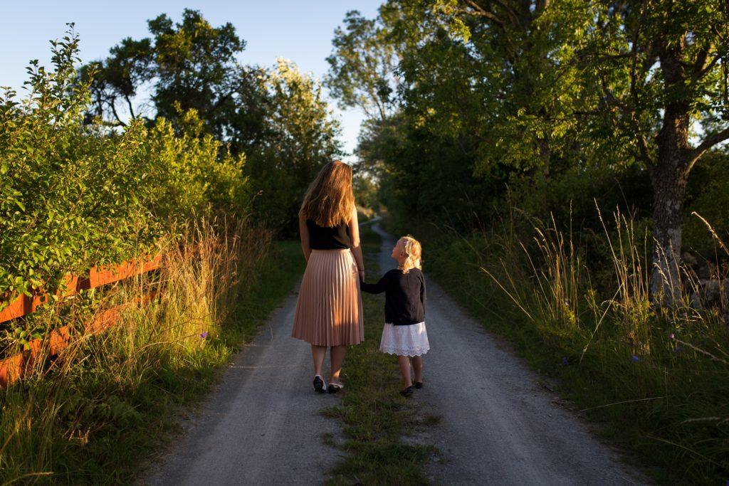 Mutter mit Tochter gehen einen Weg entlang