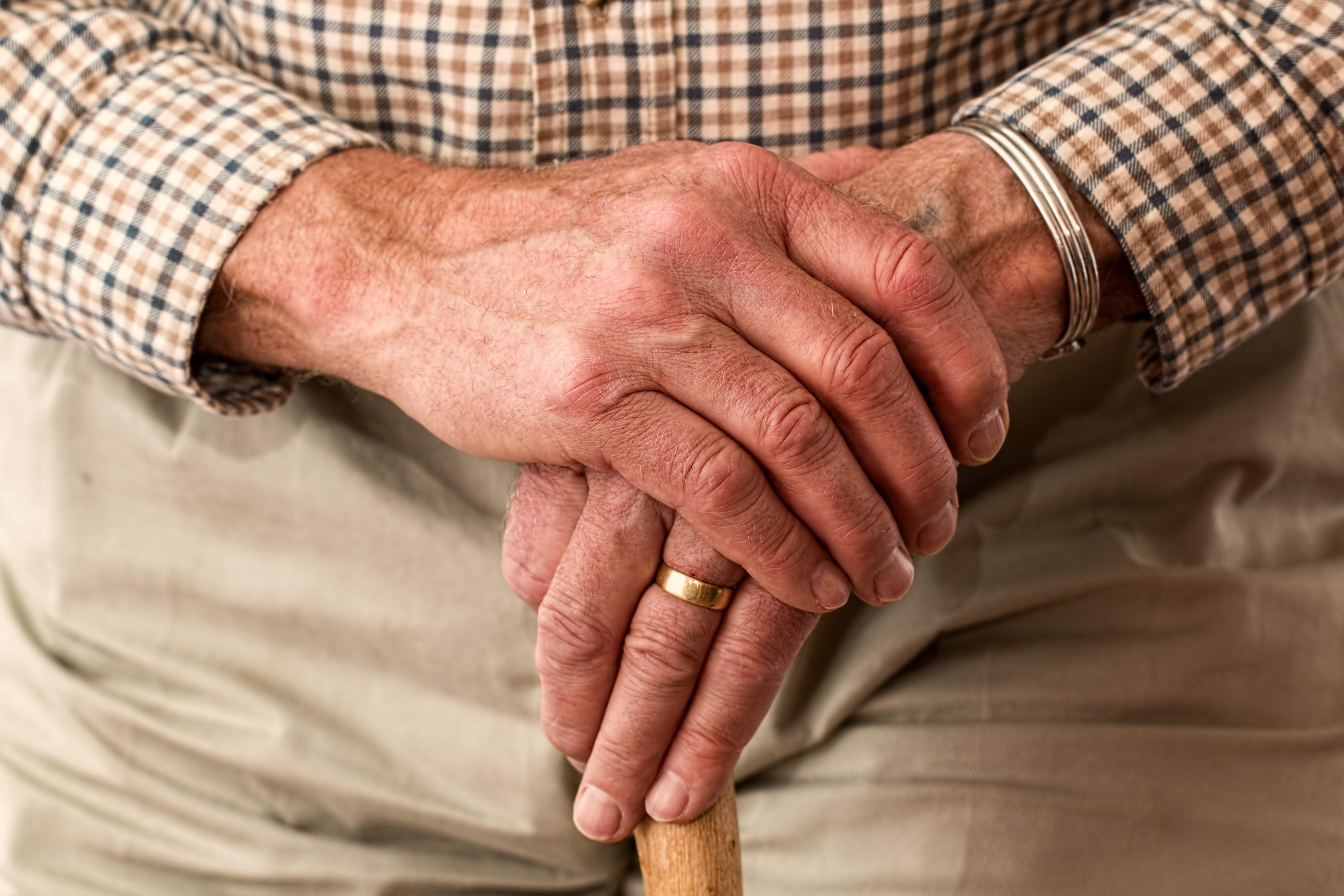 Hände eines alten Mannes lehnen auf einem Stock