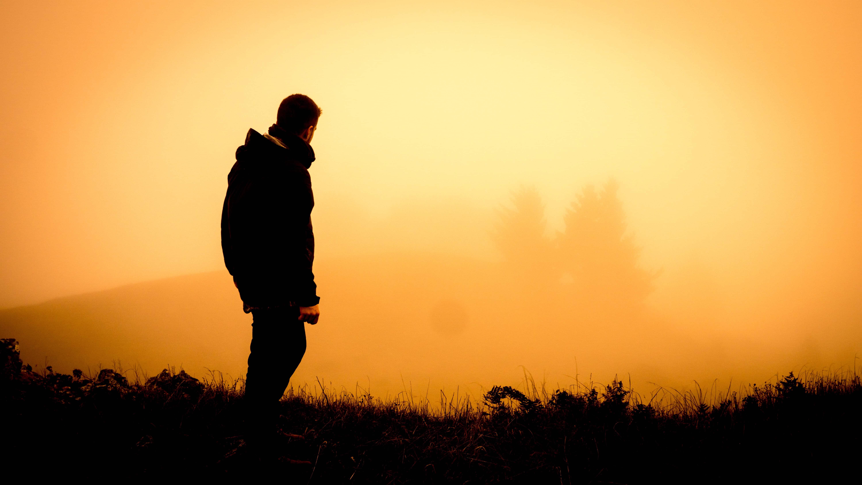 Mann blickt in nebelige Landschaft