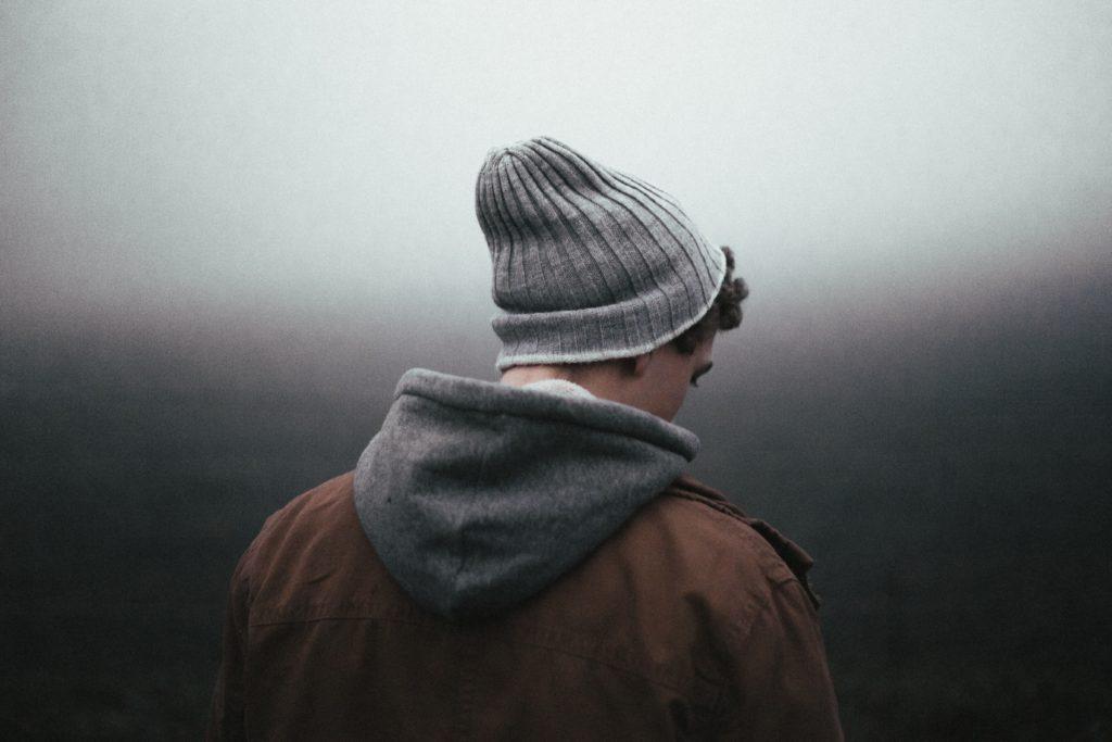 Mann vor grauem Hintergrund blickt zu Boden