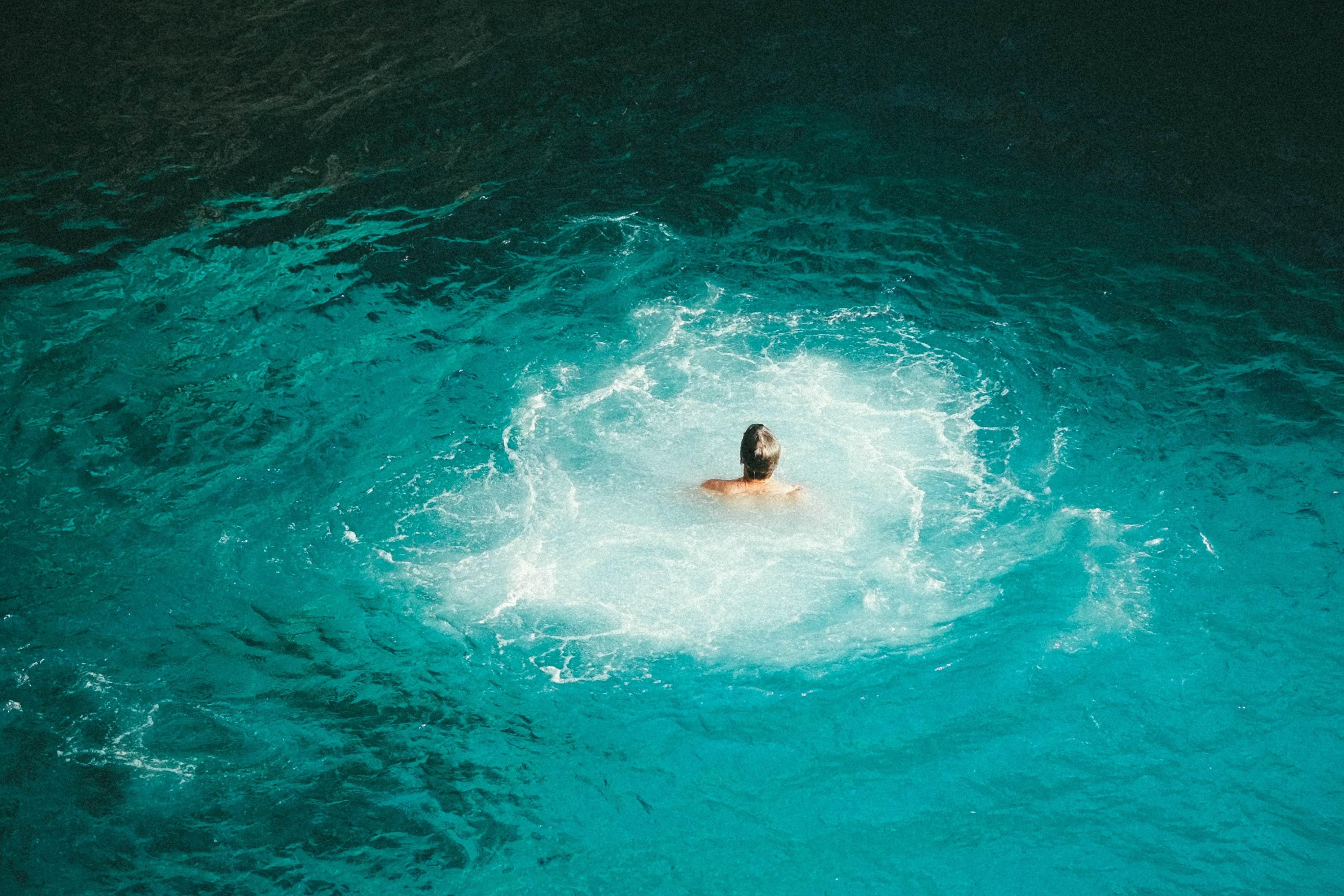 Mensch schwimmt allein im Wasser mit Strudeln
