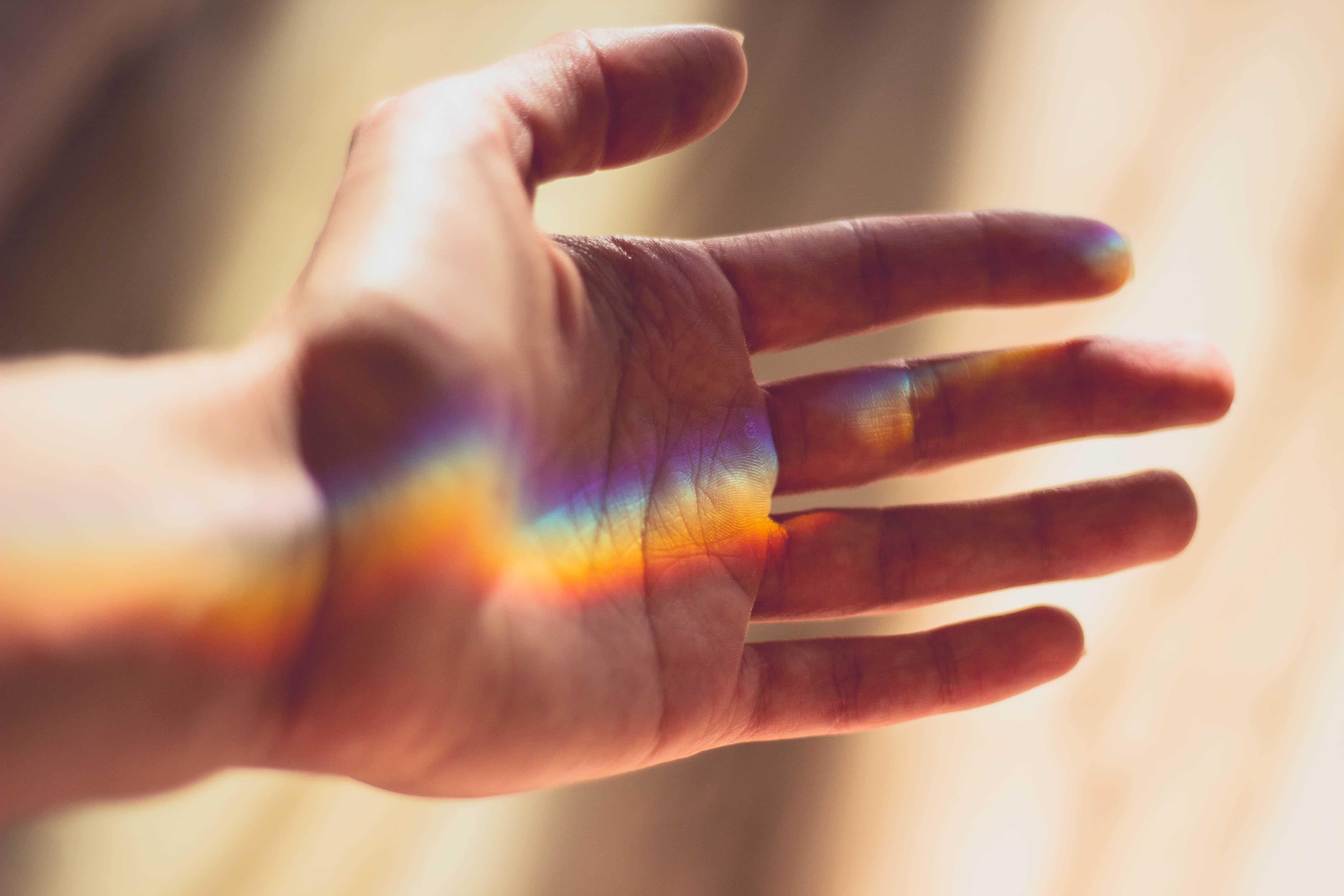 Hand, auf der sich Regenbogenfarben befinden