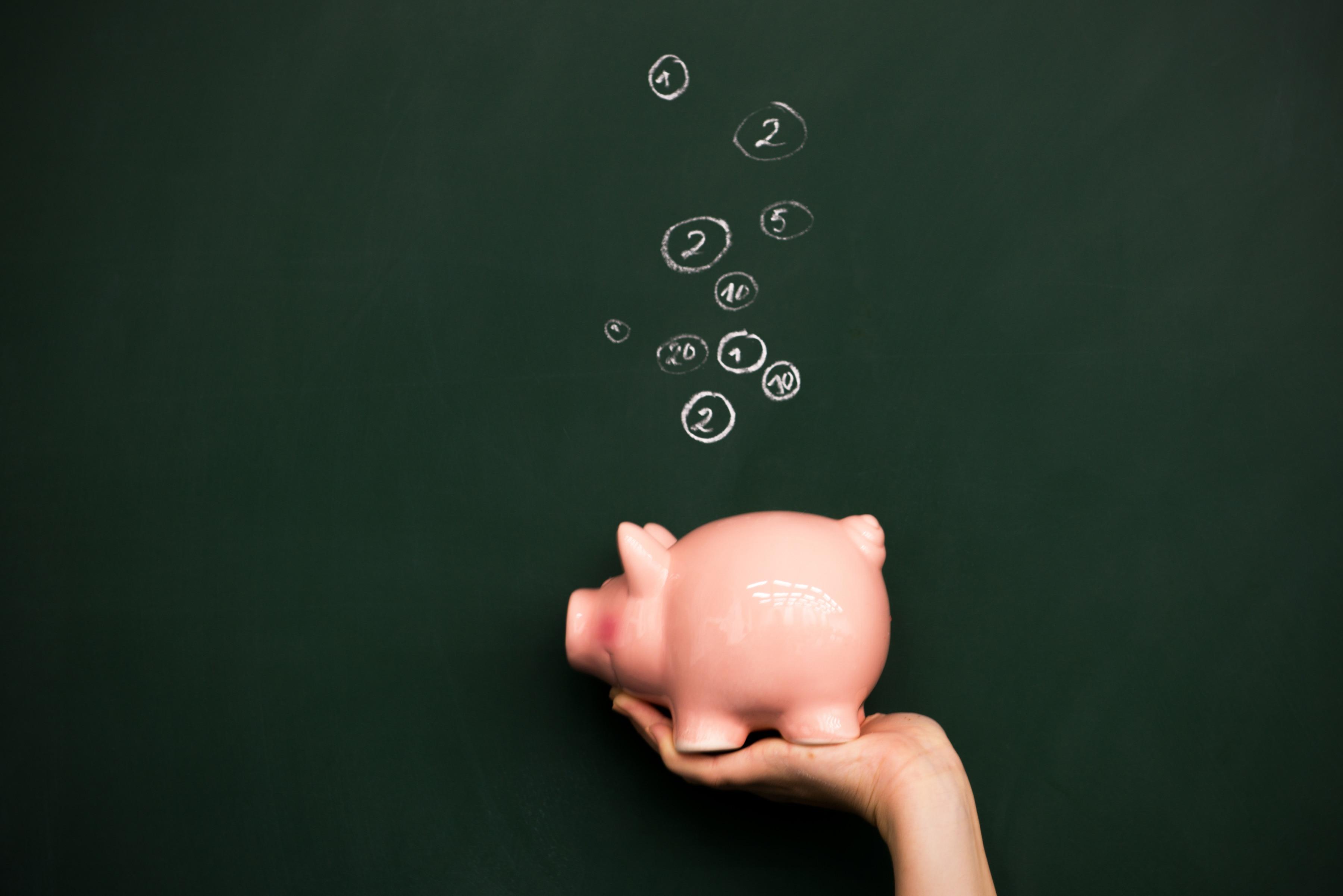 Sparschwein vor grüner Tafel mit Münzen aus Kreide