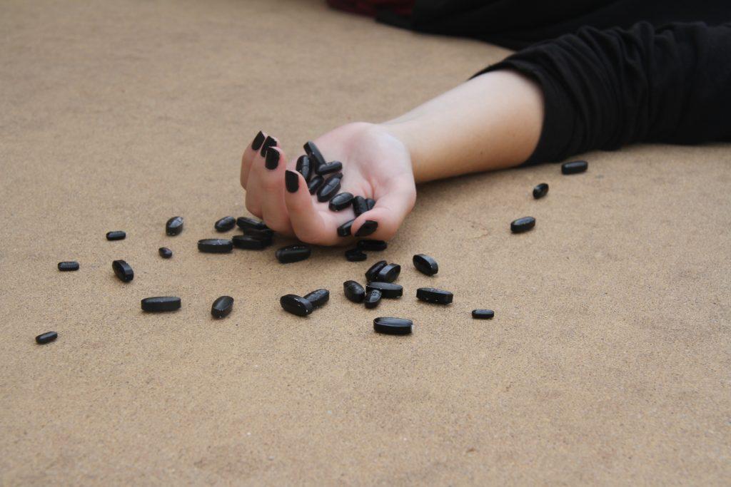 ausgestreckter Arm mit schwarzen Tabletten