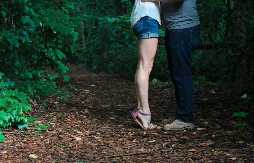 Mann und Frau stehen sich gegenüber auf einem Waldweg, nur Unterköroper zu sehen