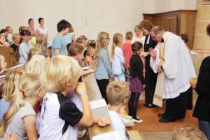 Pfarrer segnet Kinder