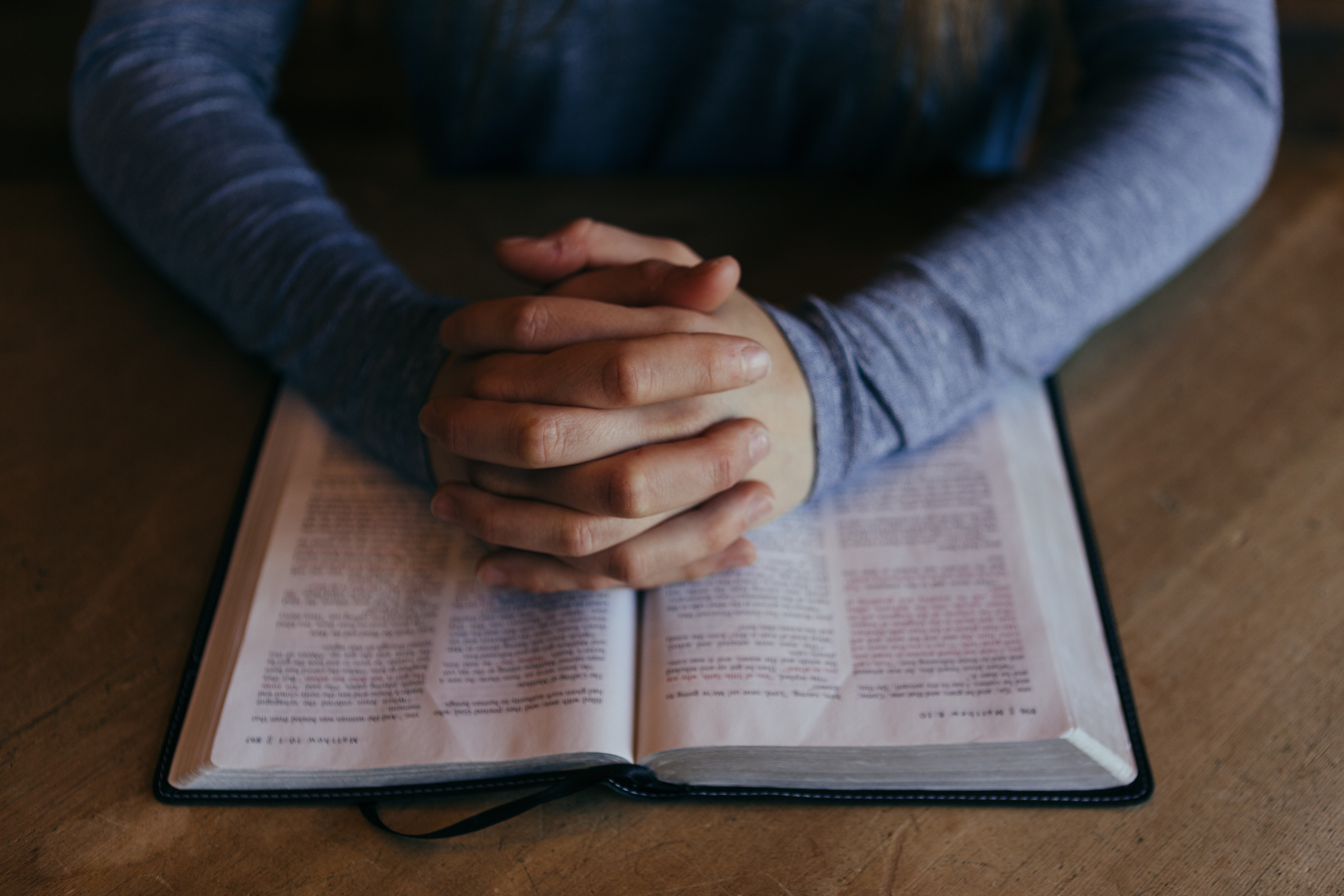 gefaltete Hände über einer aufgeschlagenen Bibel