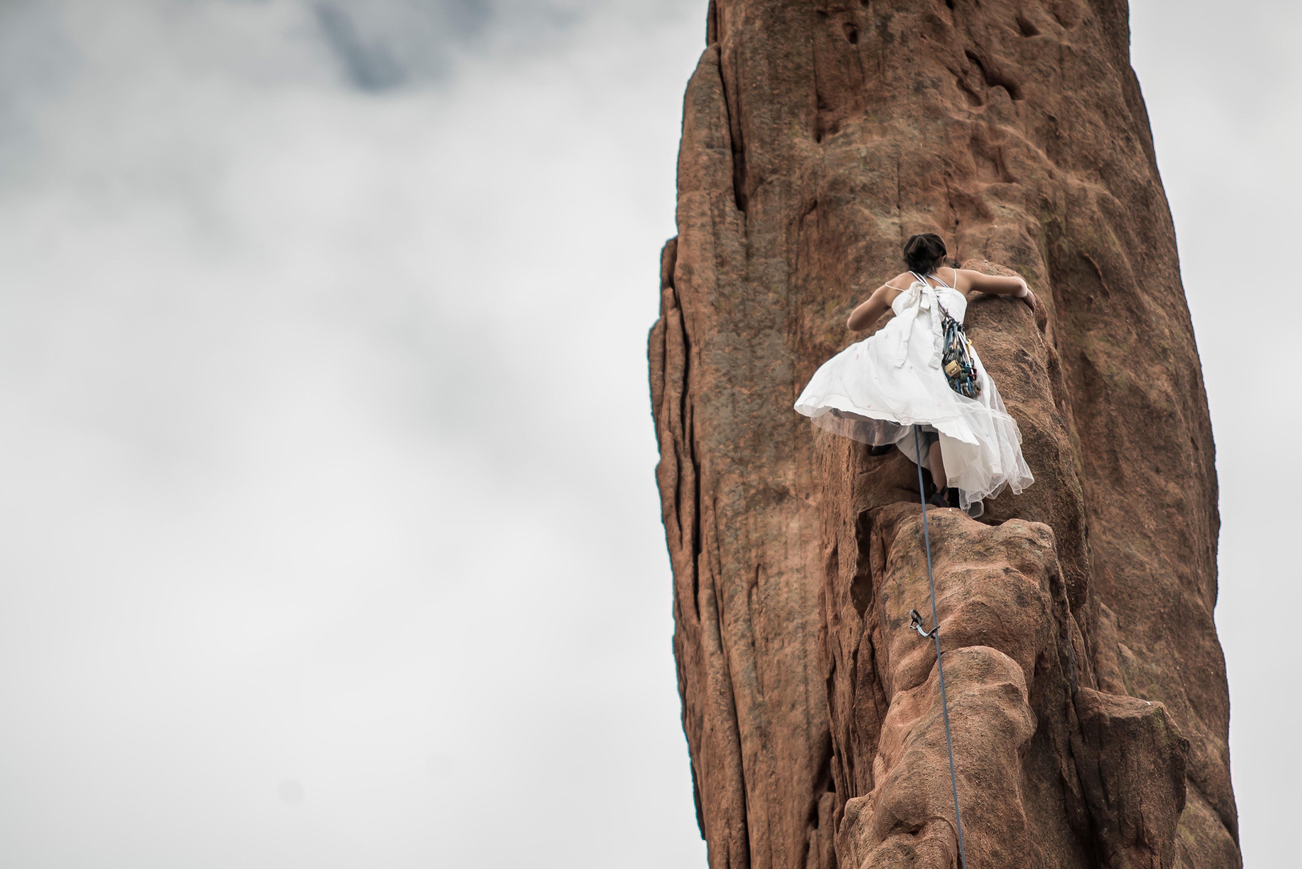 Braut klettert Felswand hoch