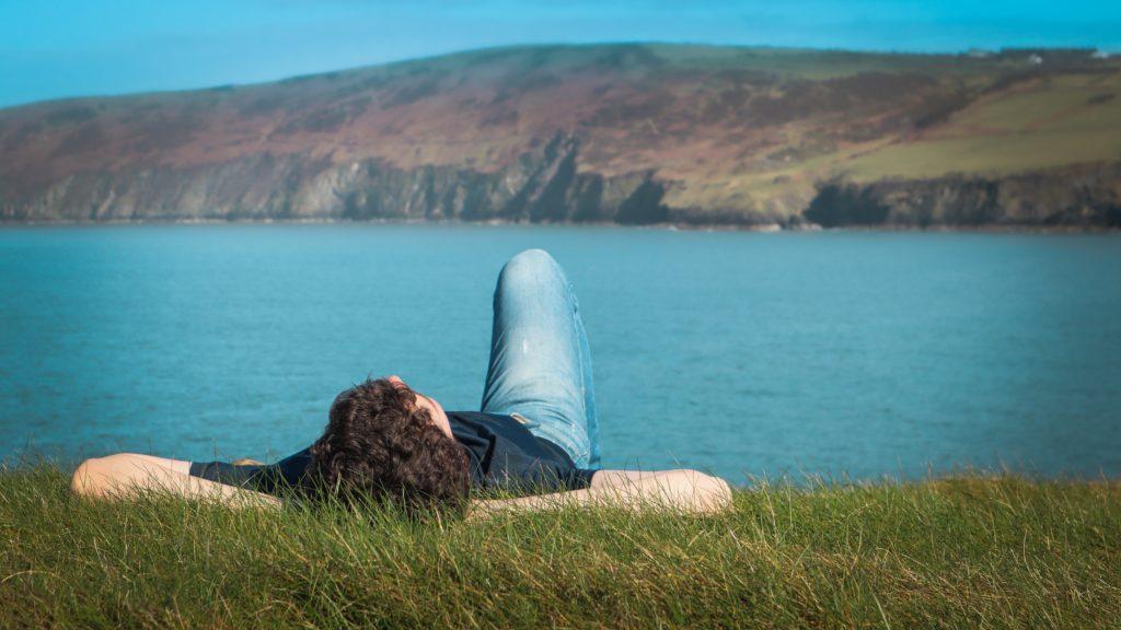 Ein Mann liegt in einer Wiese und schaut in den Himmel