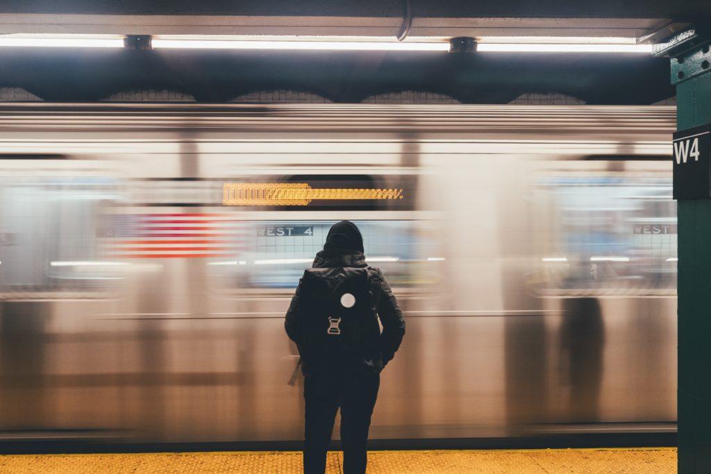 Person schaut auf fahrenden Zug