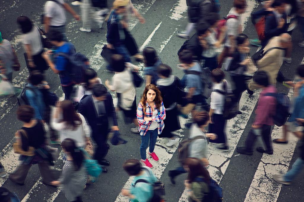 Frau steht in Menschenmasse auf Zebrastreifen