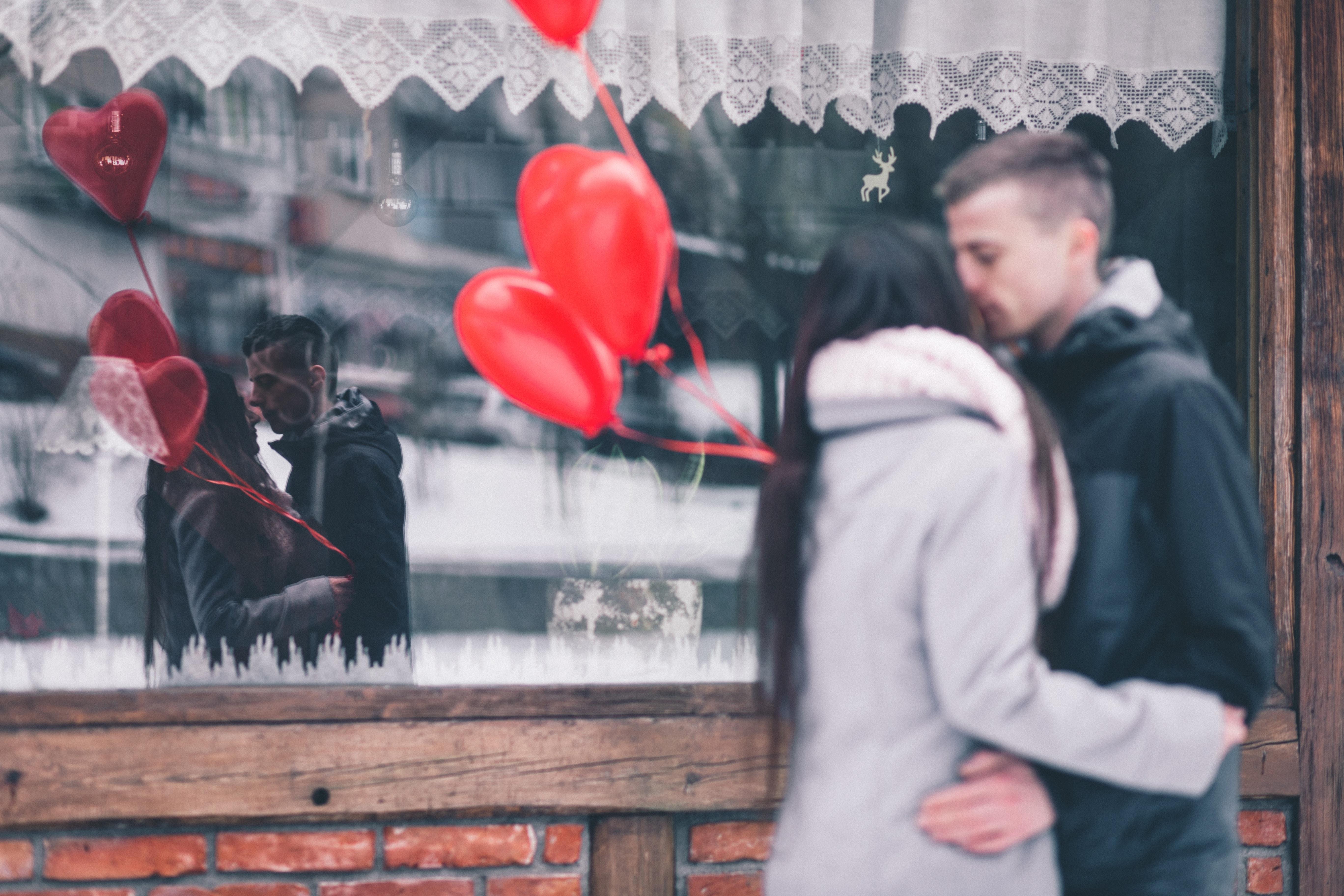junges Paar mit roten Herzluftballons