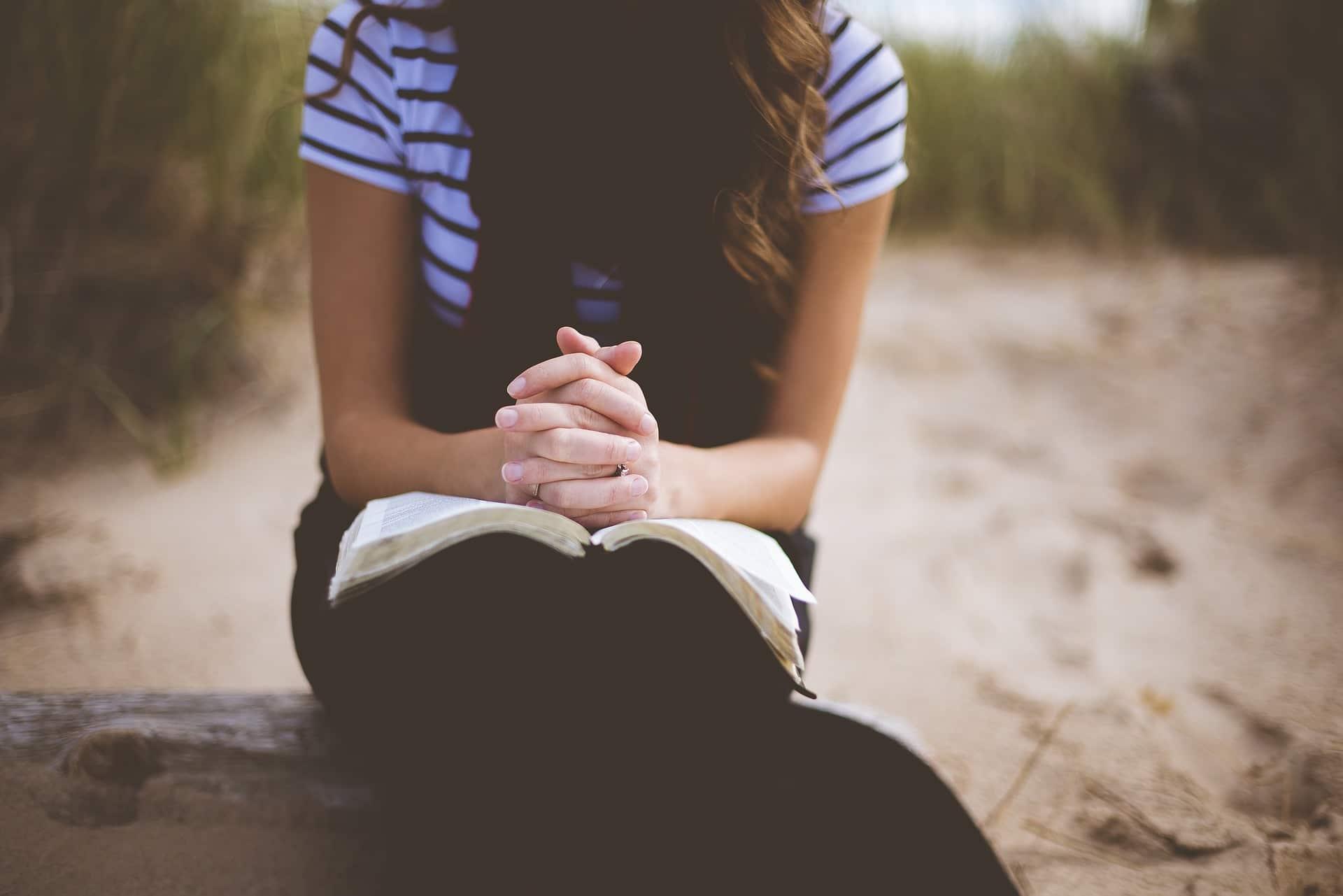 Frau betet am Strand