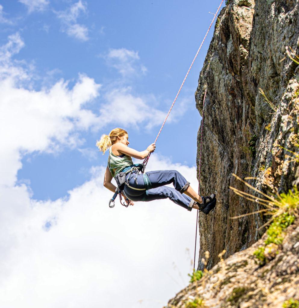 Frau klettert Felswand hoch