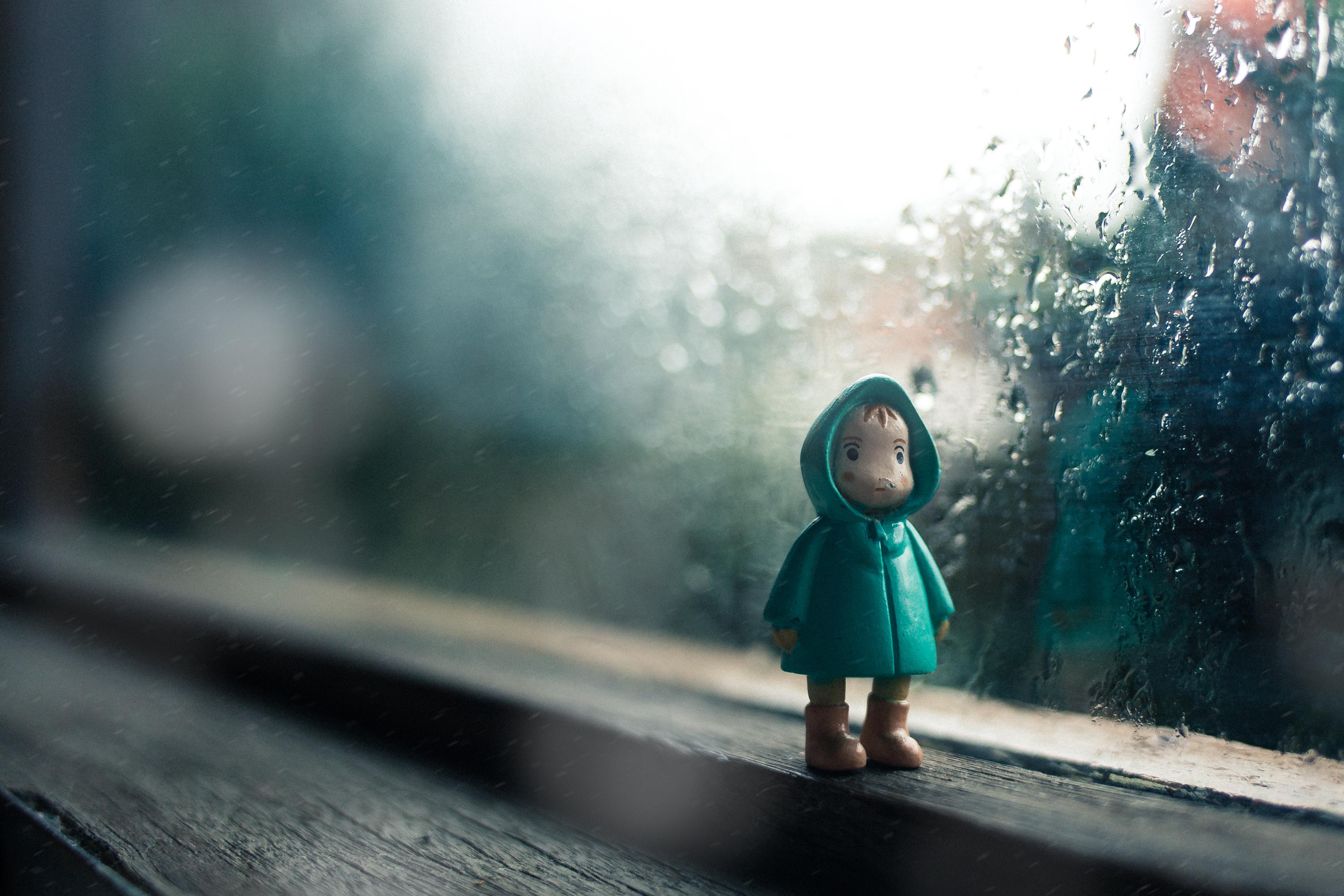 Holzfigur am Fenster, Regenwetter
