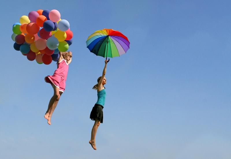 Zwei Mädchen fliegen mit bunten Ballons und einem Regenschirm durch die Luft.