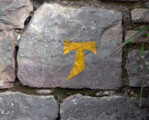 Ein Tau-Zeichen an einer Mauer