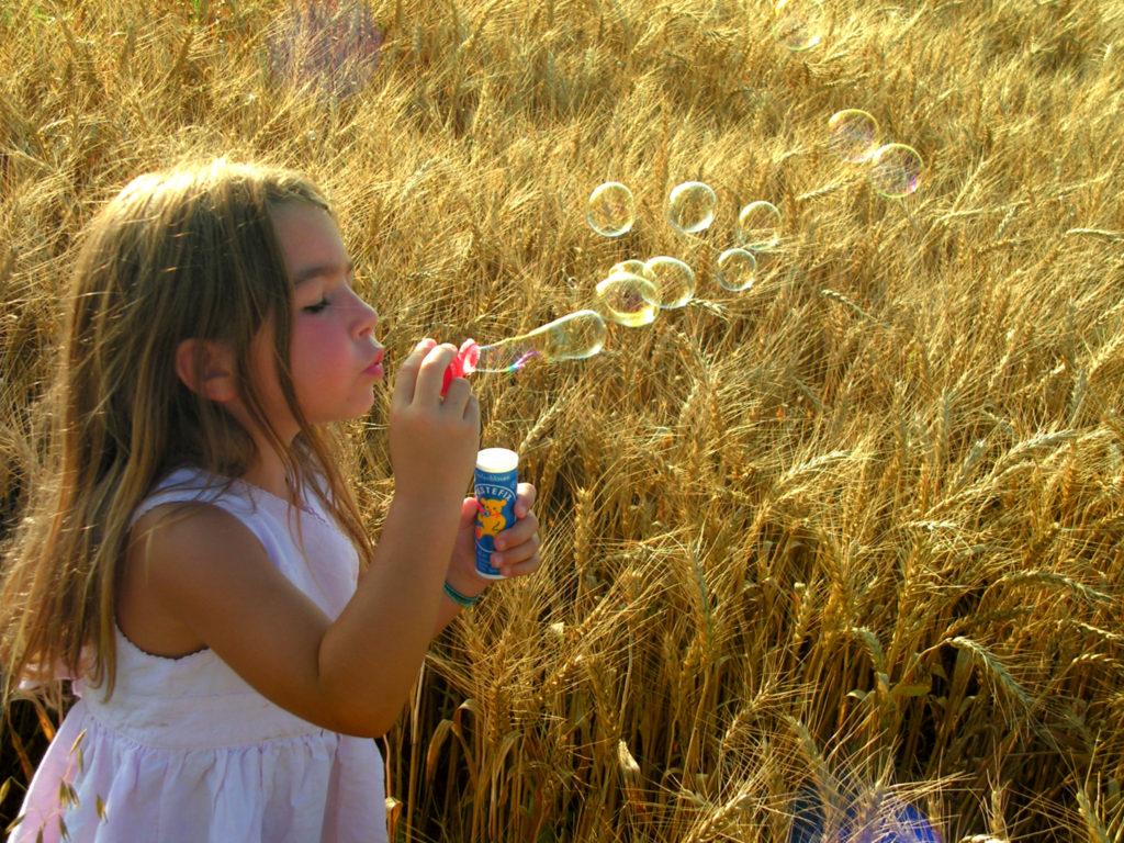Mädchen macht Seifenblasen in einem Kornfeld
