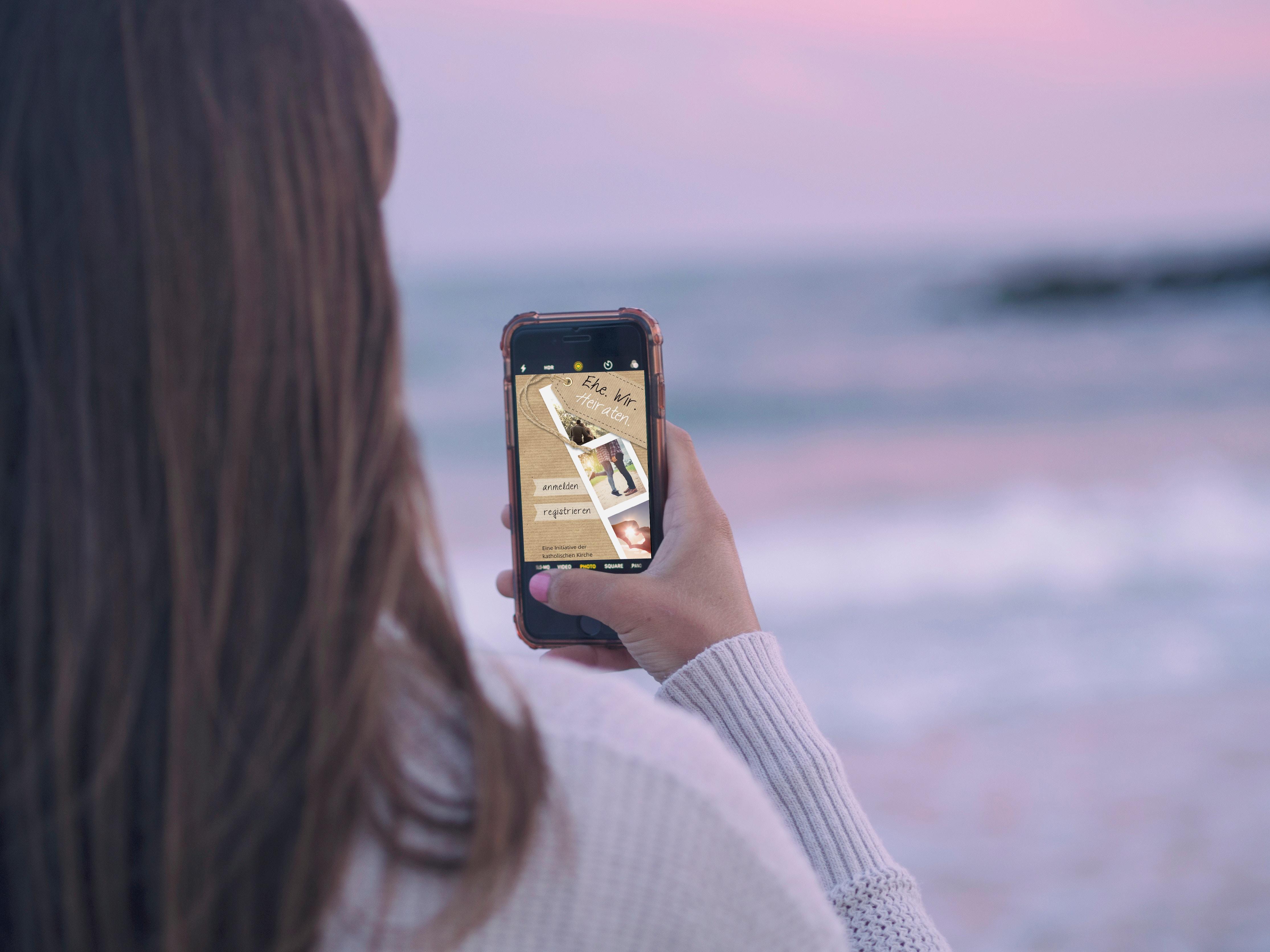 Frau mit Handy am Meer