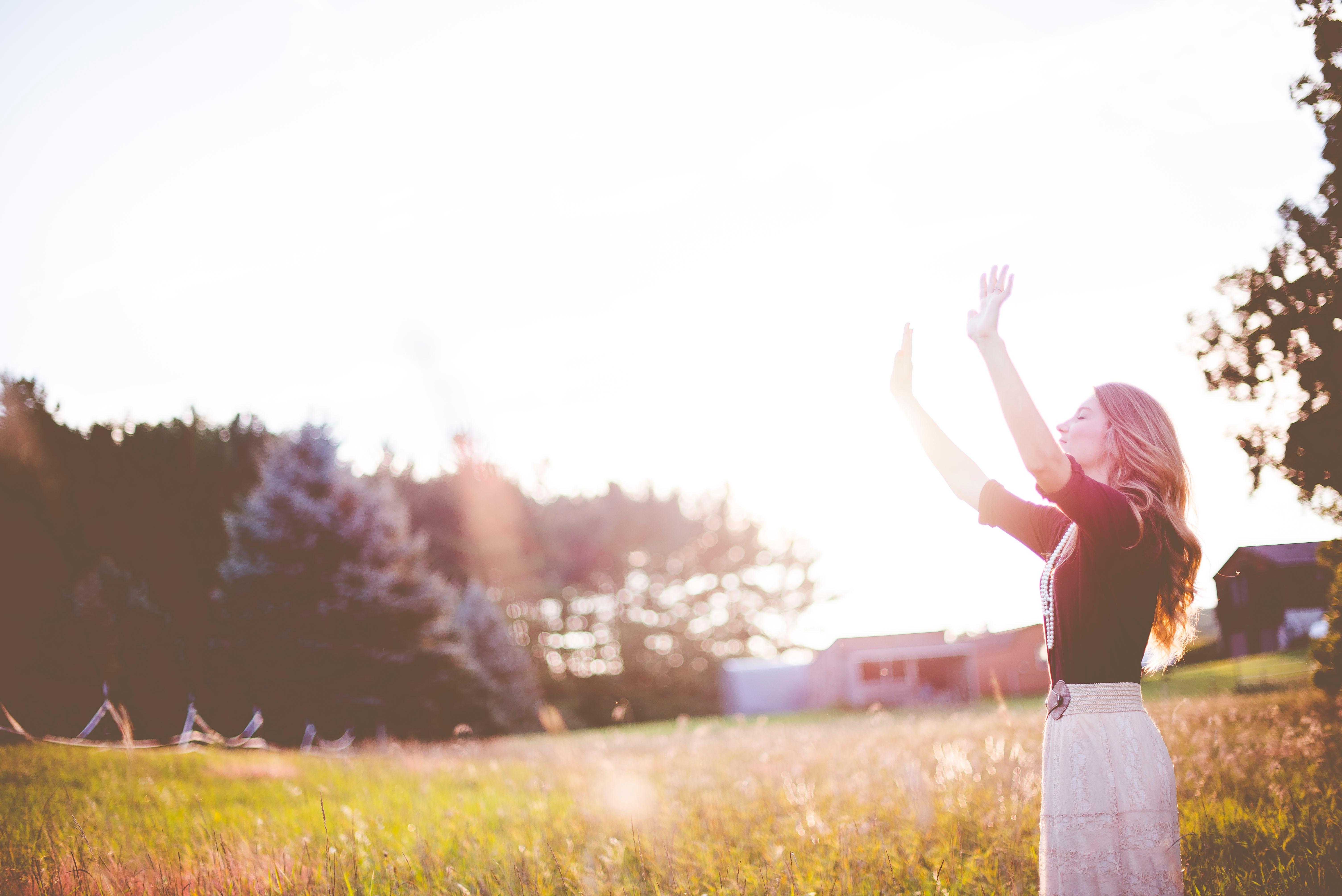 Frau hebt die Arme und blickt in den Himmel