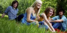 junge Menschen sitzen auf einer Wiese