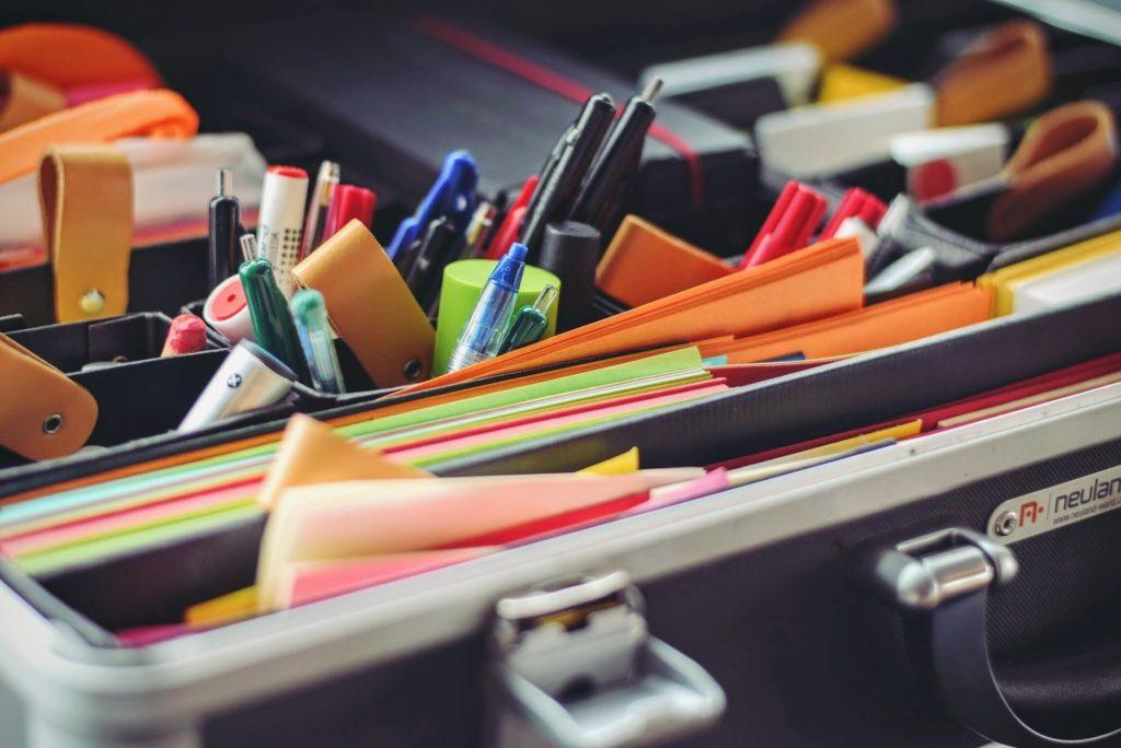 Büroutensilien wie Stifte und Blöcke sind in einem Koffer geordnet.