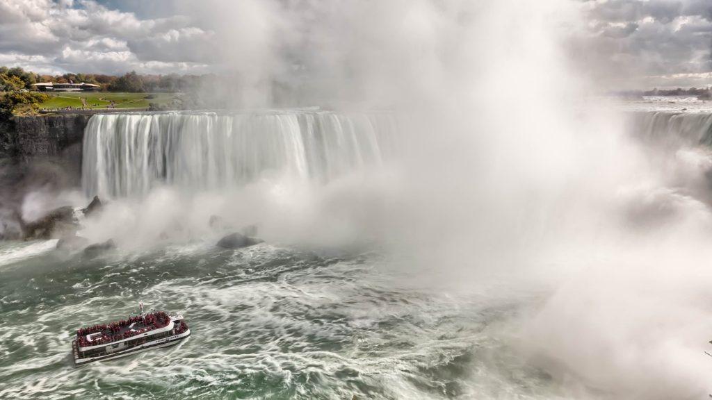 Ein Boot nähert sich einem Wasserfall.