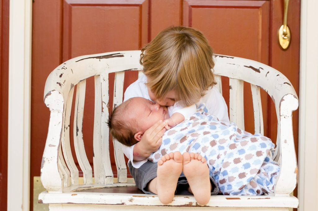 Ein Kleinkind sitzt auf einer Bank und kuschelt mit einem Säugling.