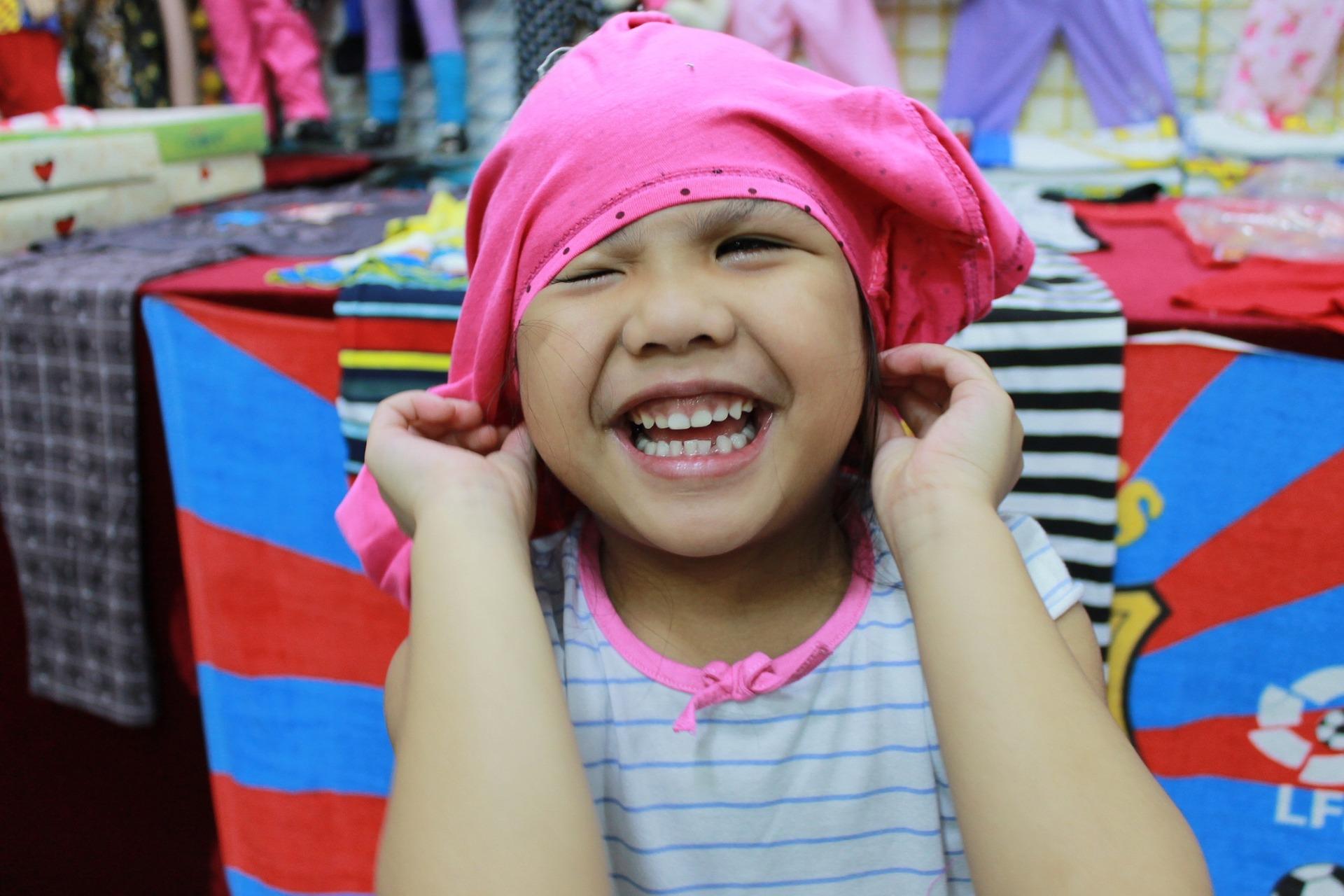 Ein kleines Mädchen will sich ein Shirt falsch herum auf den Kopf ziehen.