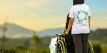 Eine Frau steht mit einem Rollstuhl in einer Naturlandschaft